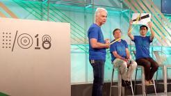 """Ein Mann hält ei Foto eines Satelliten hoch, ein anderer Mann hält ein Maßband vom """"Satelliten"""" quer über eine Bühne gespannt."""