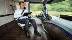 LKW-Führerstand; der Fahrer liest während der Fahrt am Tablet