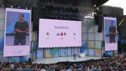 """Bühne, großer Bildschirm mit Aufschrift """"Android Go"""", Redner, Publikum"""