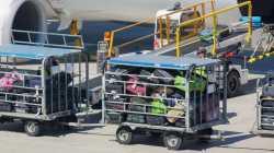 Gepäckwagen voller Koffer vor einer Flugzeugturbine