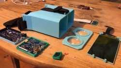 Auf einem Tisch liegen ein 3d-gedrucktes Gehäuse für eine 3D-Brille und elektronische Komponenten