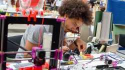 Ein junger schwarzer Mann sitzt hinter einem 3D-Drucker und lötet Bauteile