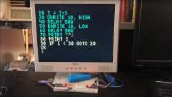 Auf einem Monitor ist großformatige Schrift zu sehen. Darunter sind auf einem Breadboard zwei kleine Arduino Nanos.