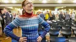 Eine Frau steht in einem Vortragsraum, ihr Pullover ist geringelt mit blauen und roten Streifen.