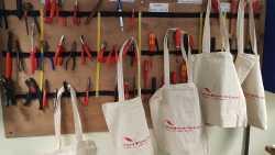 An einer Wand hängen Werkzeuge und Taschen.