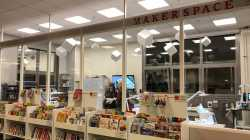 Ein großer Glaskasten, vor dem mehrere Regale mit Büchern stehen. Innen sind ein paar Personen neben Maschinen zu erkennen.