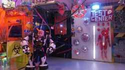 """Ein Roboter mit Puppenkopf steht vor einer beleuchteten Kulisse mit """"Häuserfronten"""" von Biochip Corp, Borghain und einem Testcenter."""