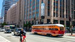Gebäude, davor eine orange Straßenbahn und ein Radfahrer