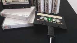 Auf einem Regal stehen mehrere Kassetten. An einer ist ein Kabel angeschlossen