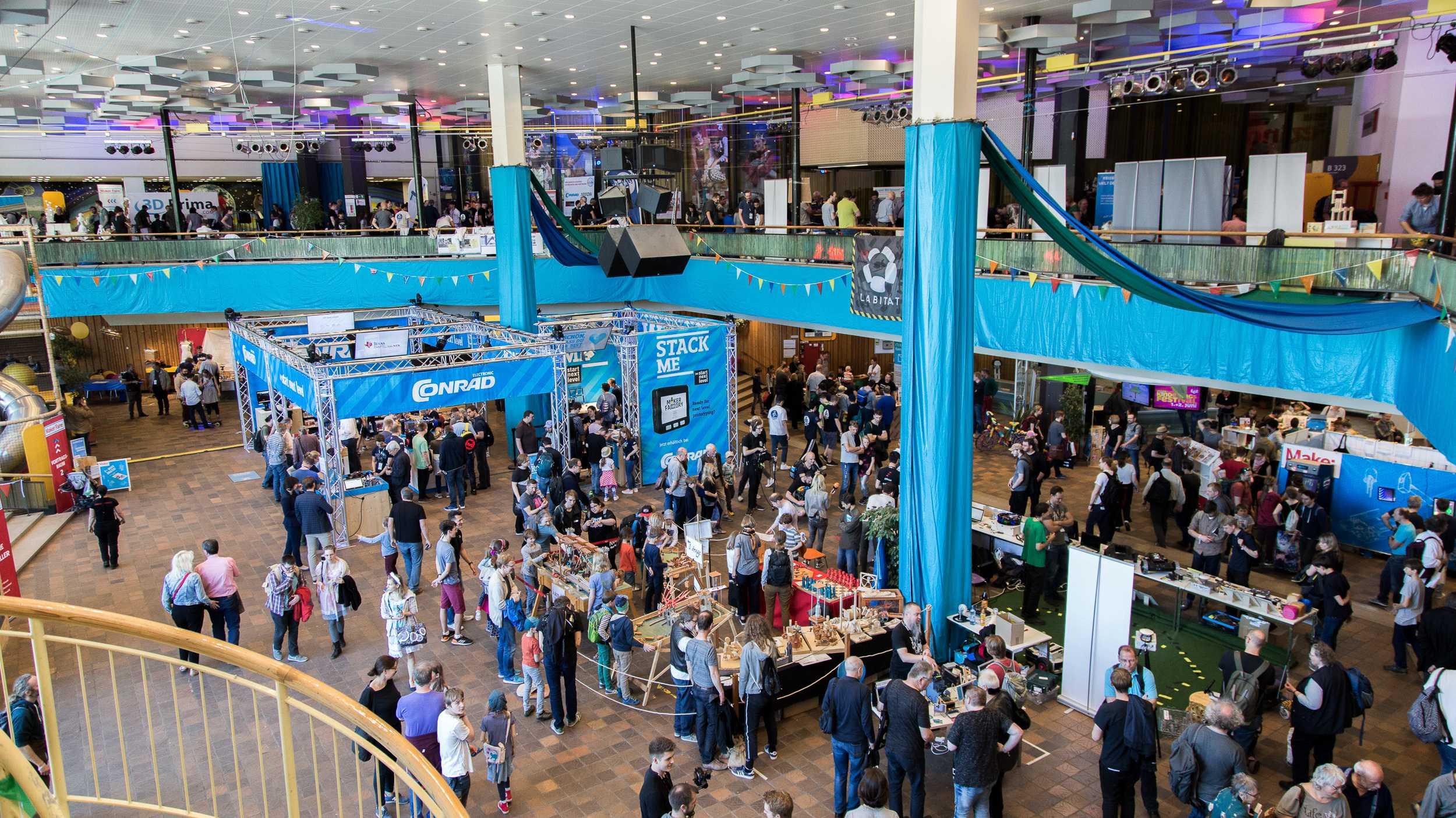 Blick in das Foyer des FEZ Berlin mit Ständen und Menschen während der Maker Faire Berlin 2019.