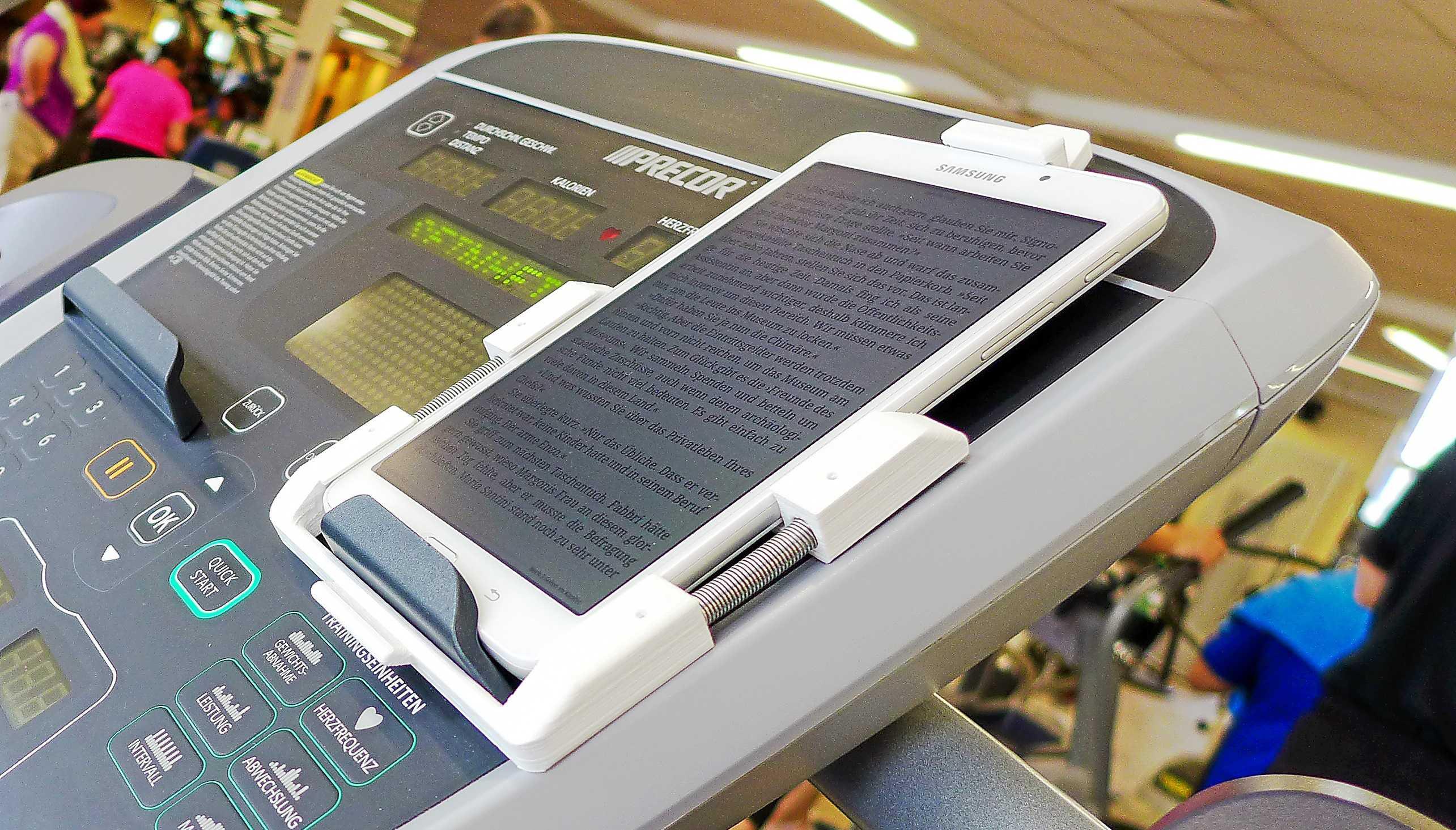 Auf dem Kontrollpaneel eines Laufbands liegt ein Tablet in einer 3D-gedruckten Halterung.