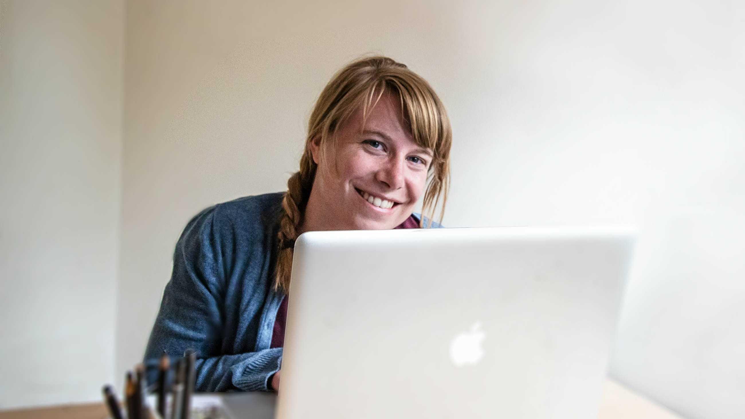 Blonde Frau lächelt inter Macbook hervor