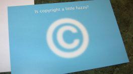 """Blaues Schild """"Is copyright a little fuzzy?"""" mit unscharfem Copyright-Symbol"""
