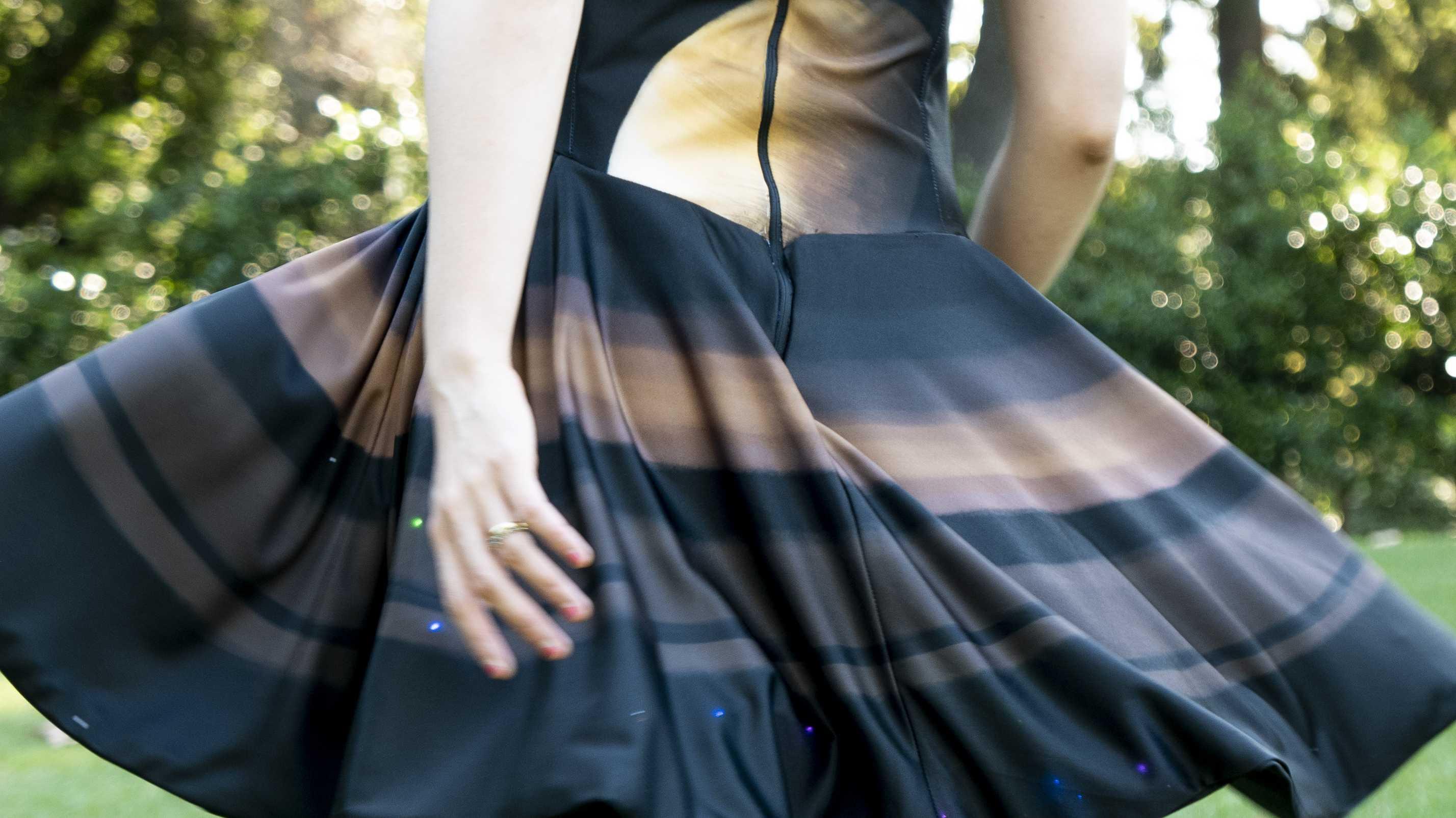 Eine Person trägt ein Kleid, dessen Rock durch die Luft schwingt, darauf leuchten LEDs.