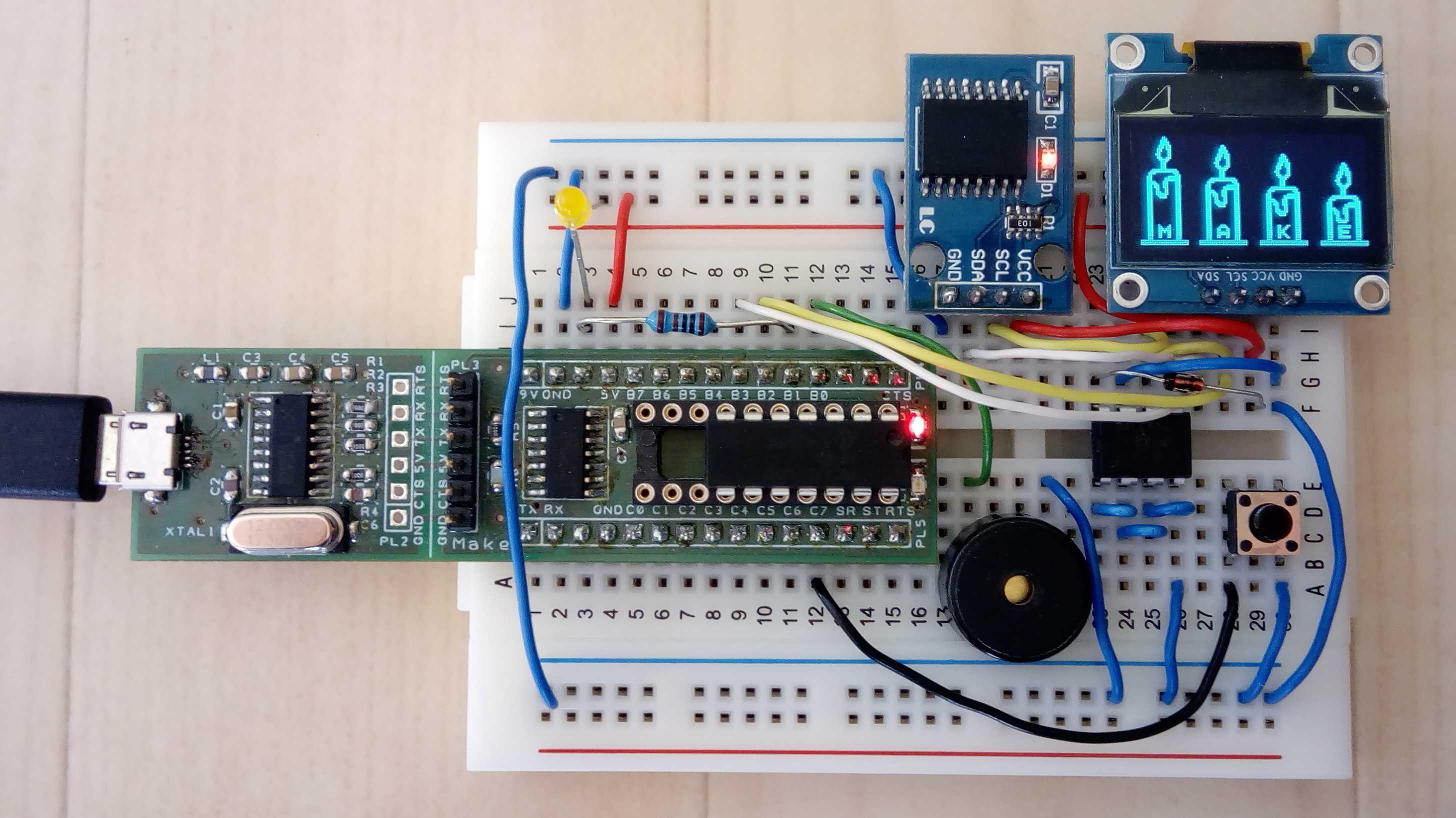 """Steckbrettaufbau mit Nano-Axe-Board, OLED, Piezo-Summer und Echtzeituhr. Auf dem OLED """"leuchten"""" vier Kerzen."""