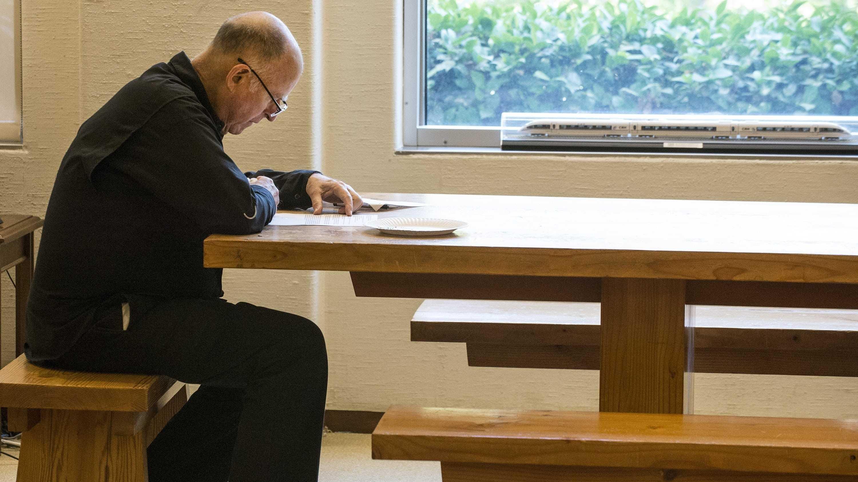 Jerry Brown lesend an Holztisch