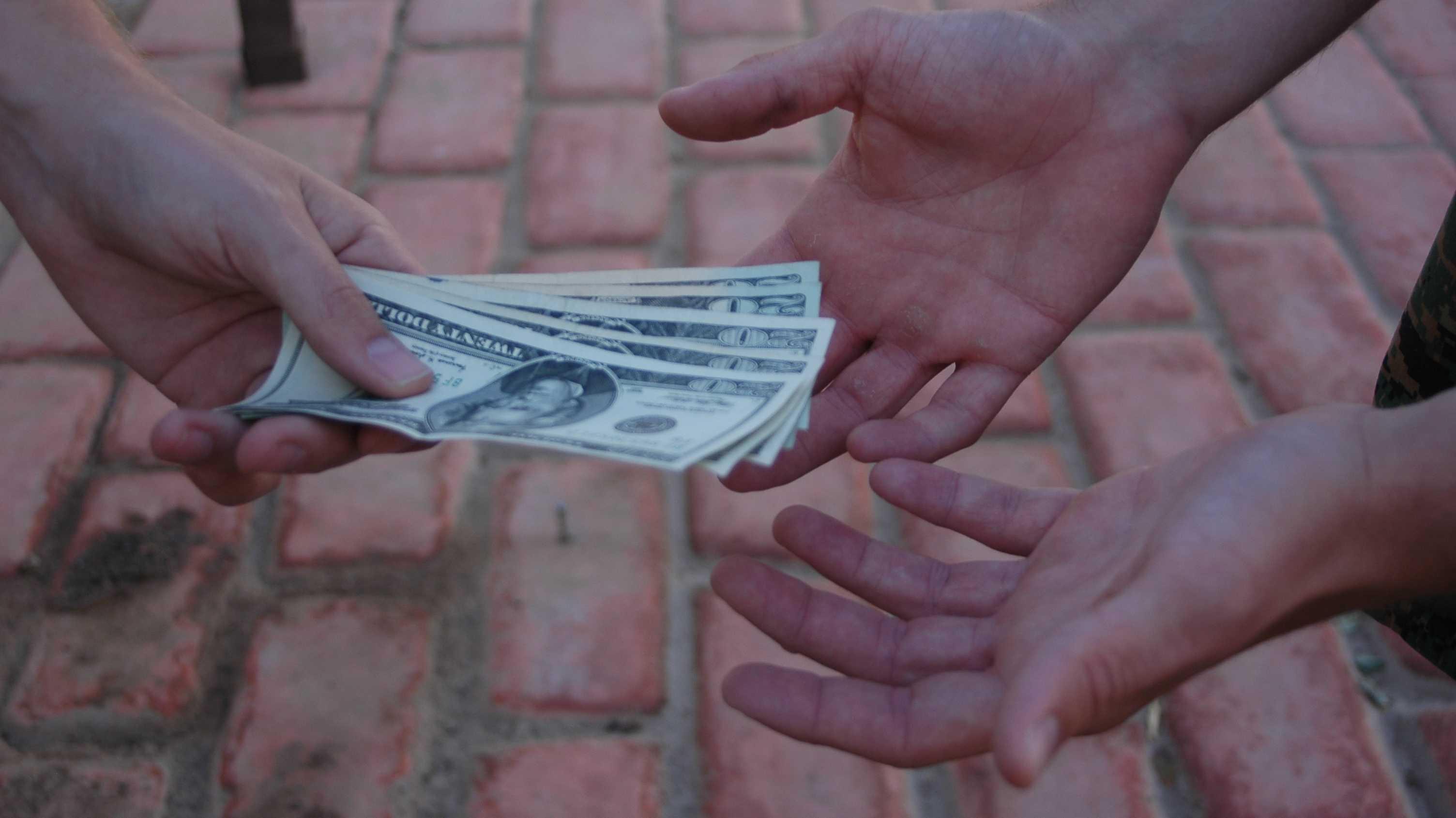 Eine Hand reicht Dollarscheine, zwei Hände empfangen sie