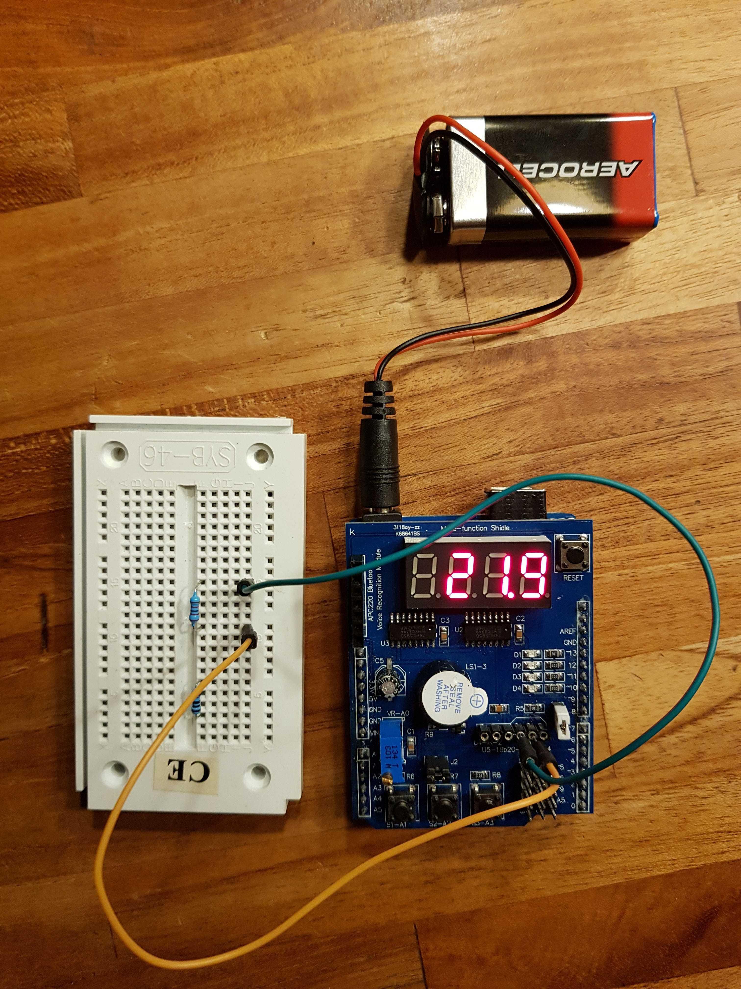 Blaues Shield neben weißem Breadboard mit zwei Widerständen und einer Batterie.