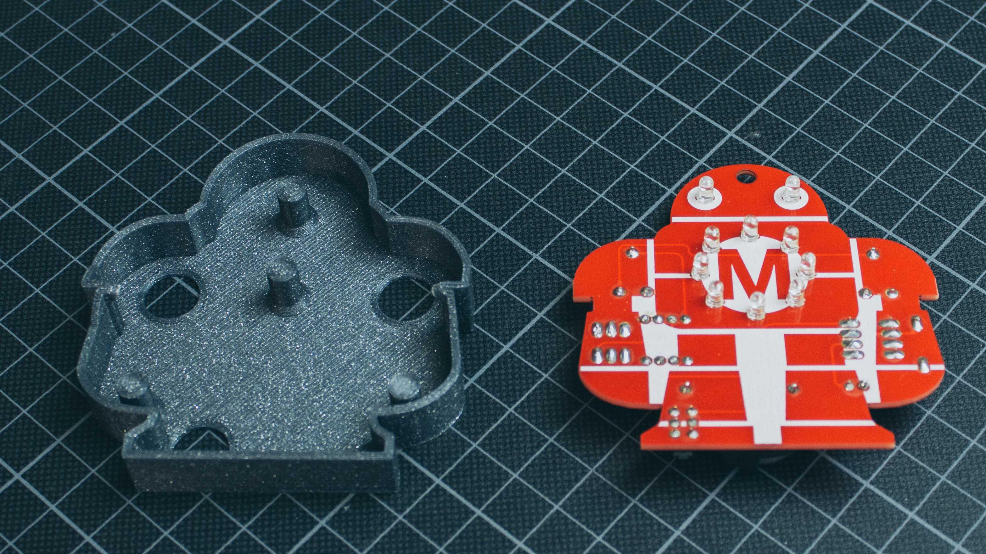 Auf einer Millimetermatte liegen eine rote Platine in Form eines Roboters und daneben ein Gehäuse aus dem 3D-Drucker.