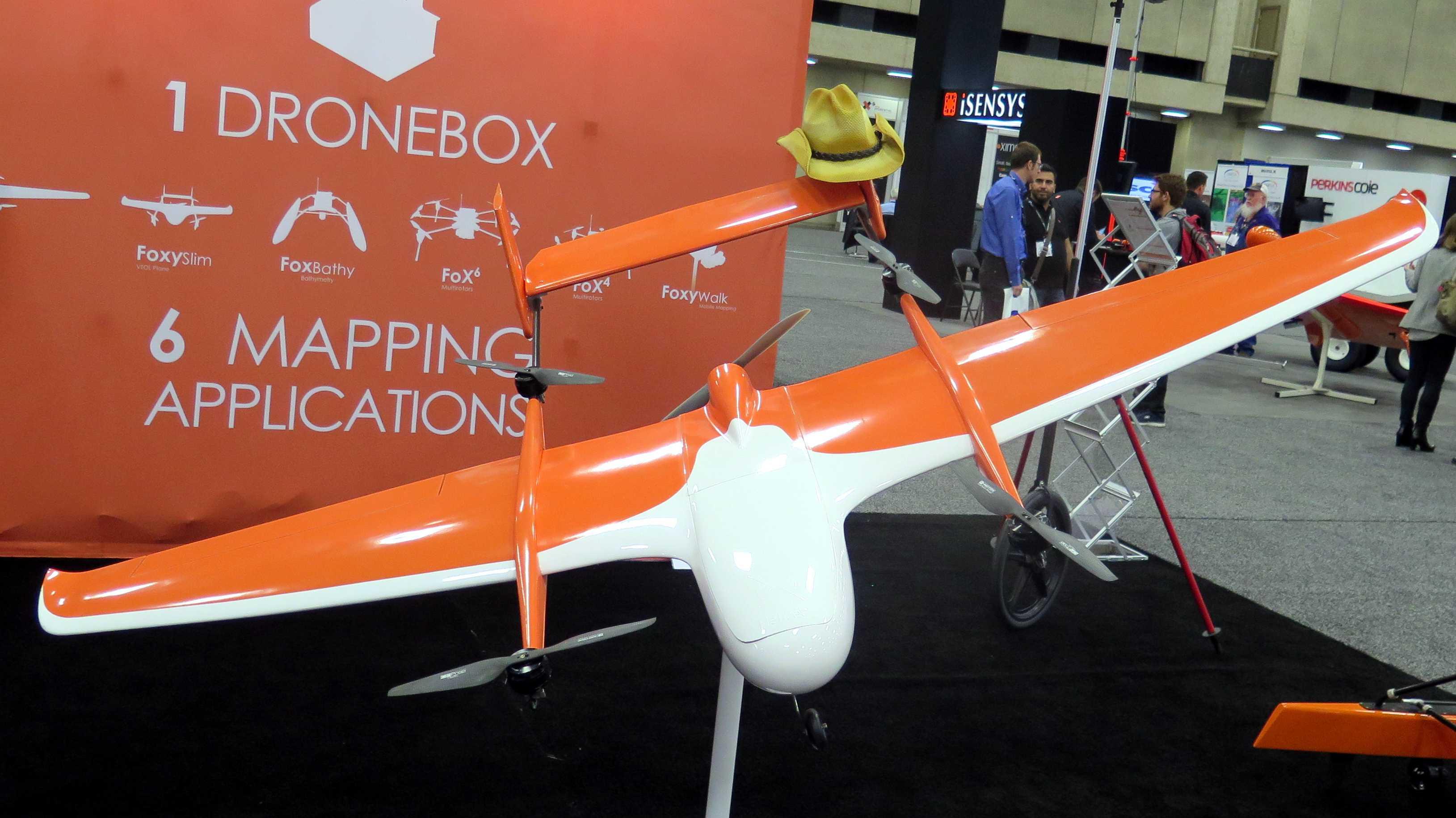 Orange-Weiße Flugdrohne mit einem aufgesetztem Hut steht auf einem Ständer
