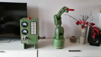 Ein grüner Roboter-Arm neben einem grünen Schaltgehäuse und einer Vase mit roten Blumen