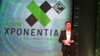 Xponential-Logo, davor ein weißer Mann im Businessanzug