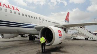 Mann in Warmweste lugt in das Triebwerk eines A320