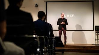 """Dara Khosrowshahi vor einer Leinwand mit Aufschrift """"Uber"""""""