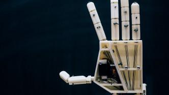 Eine weiße Roboterhand vor schwarzer Wand