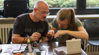 Ein Mann und ein Mädchen beugen sich über ein Elektronikprojekt