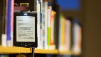 Ein E-Book-Reader steht in Mitten von Büchern im Regal.