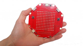 Eine Hand hält eine rote Platine mit acht Seiten, auf der 144 LEDs verbaut sind