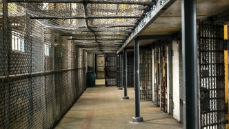 Vergitterter Gang in einem Gefängnis, rechts Zellentüren