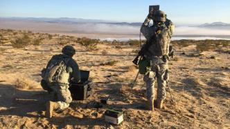 2 Soldaten in Tarnkleidung hantieren mit technischen Geräten