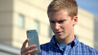 Junger Mann blickt stirnrunzelnd auf sein Handy