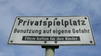 Ein Schild vor blauem Himmel, die Aufschrift lautet: Privatspielplatz - Benutzung auf eigene Gefahr - Eltern haften für ihre Kinder