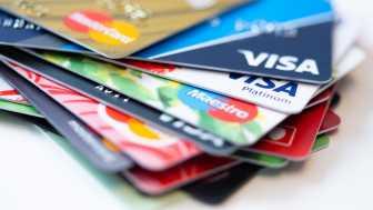 Ein ungeordneter Stapel mit Kreditkarten und Girokarten von verschiedenen Zahlungsdienstleistern wie Mastercard oder Visa.