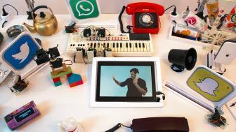 Auf einem weißen Schreibtisch steht ein Tablet, darum herum sind ein Mini-Keyboard, ein Wählscheibentelefon und Icons mit Social-Media-Logos verteilt