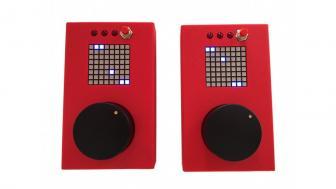 Zwei rote Handheldgeräte mit pixeligem Display und schwarzem runden Button