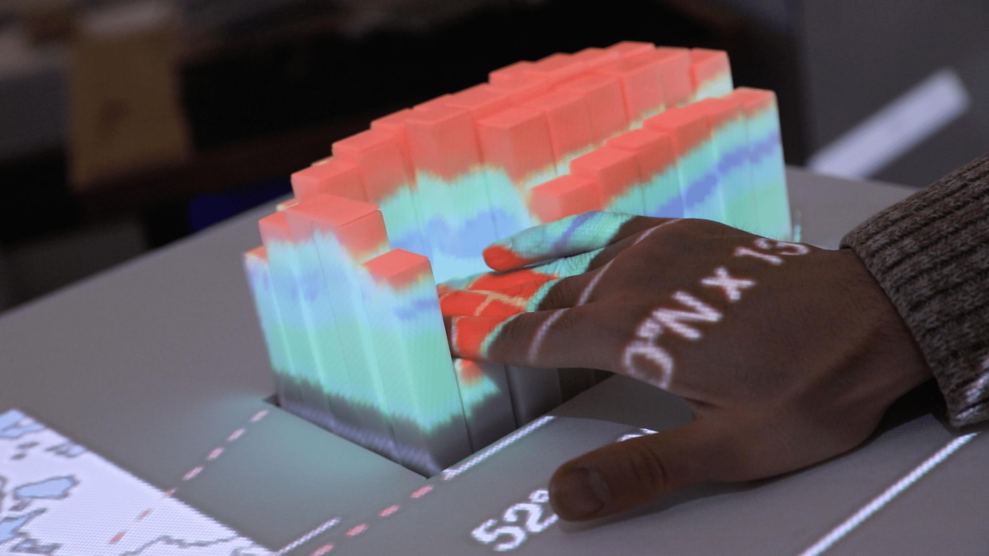 Eine Hand drückt schmale Quader in einen Tisch. Die Quader werden in verschiedenen Farben angeleuchtet.