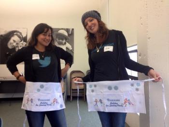 Die Twitter-Mitarbeiterinnen Cristina und Ana legen Schürzen an.