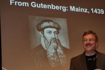 McCann im Vortrag vor Bild von Gutenberg