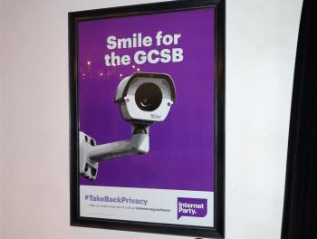 """Plakat mit Überwachungskamera und slogan """"Smile for the GCSB"""""""