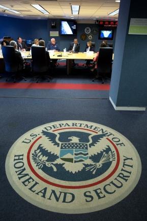 Vorderung: Siegel des Ministerium für Heimatsicherheit; Hintergrund: Leute sitzen an einem großen Konferenztisch