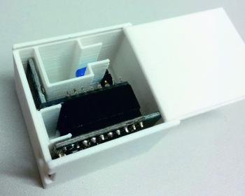 Blick in ein weißes Kistchen mit mehreren Innenwänden, an denen elektronische Bauteile befestigt sind