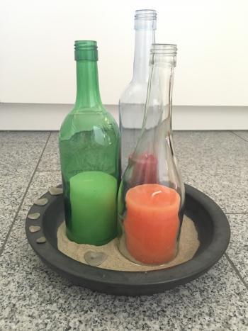 Auf einem Sandbett stehen Glasflaschen, in denen große Kerzen stehen.