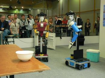 Dynamaid (links) und Cosero kooperieren bei der Küchenarbeit und katapultieren damit das Team NimbRo auf den ersten Platz im Wettbewerb der RoboCup@home League.