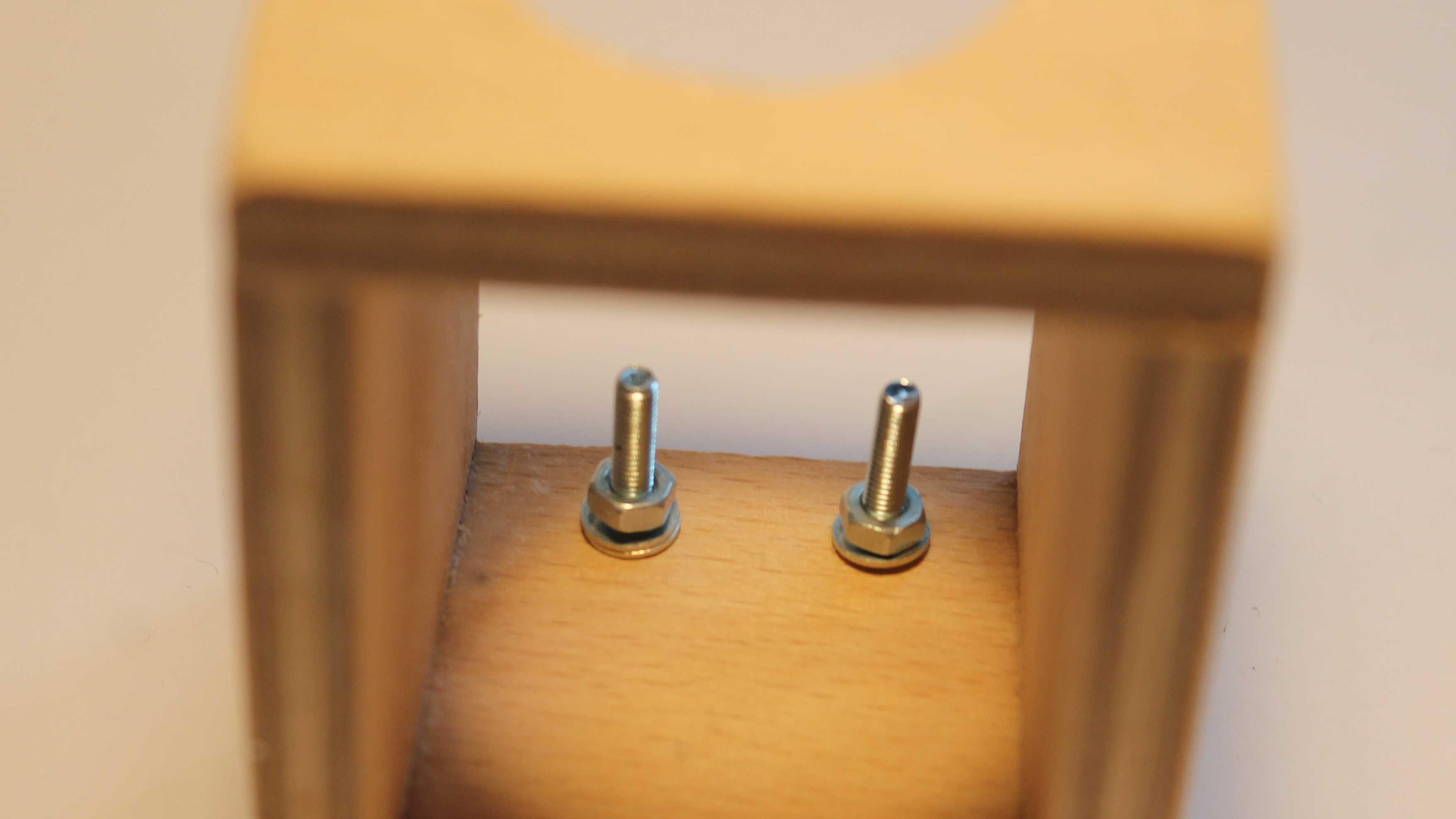 Zwei Schrauben ragen aus einem Stück Holz.