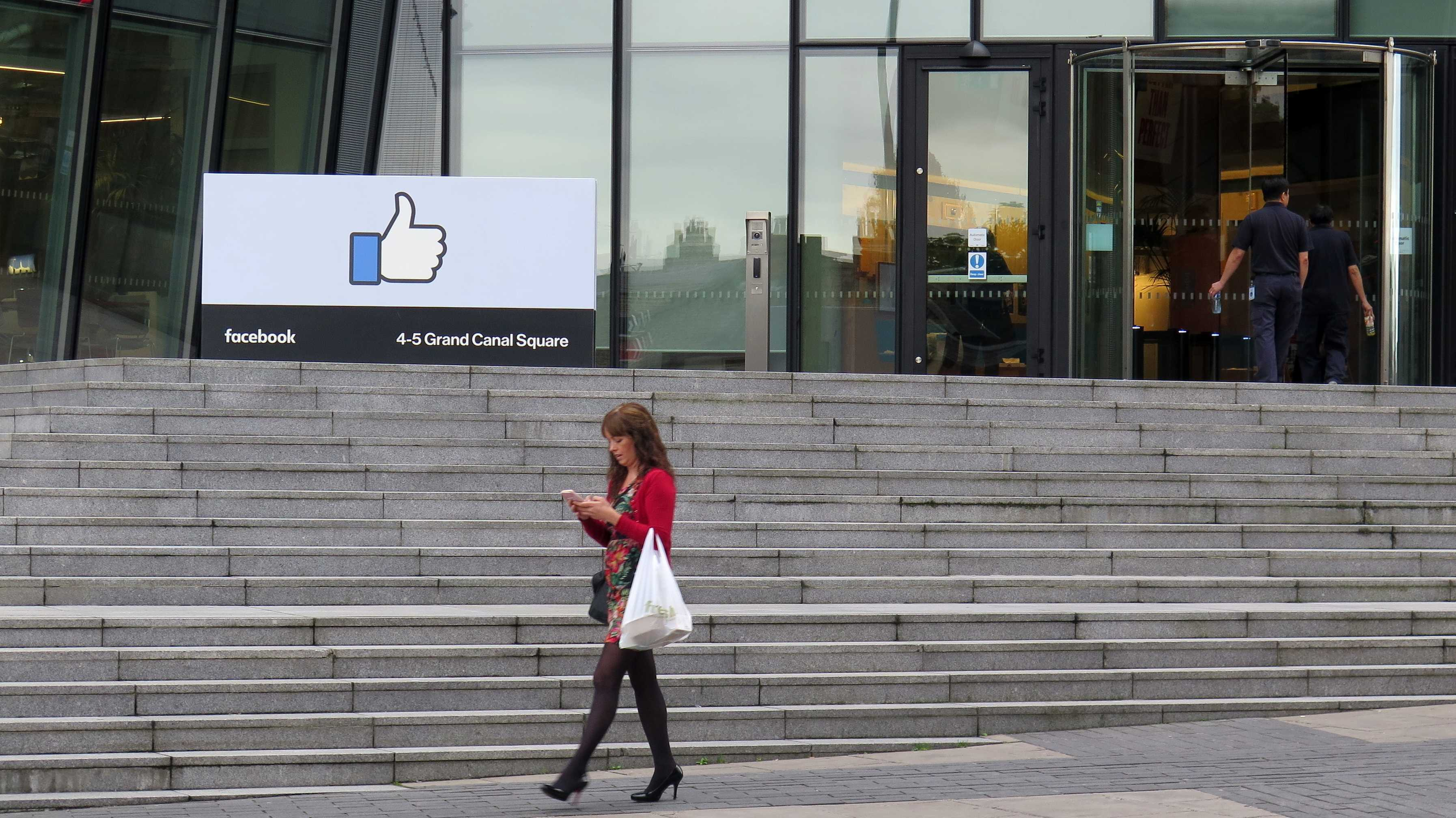 Großes Like-Logo vor Glaspalast, davor auf Handy blickende Frau in Strümpfen und roter Weste