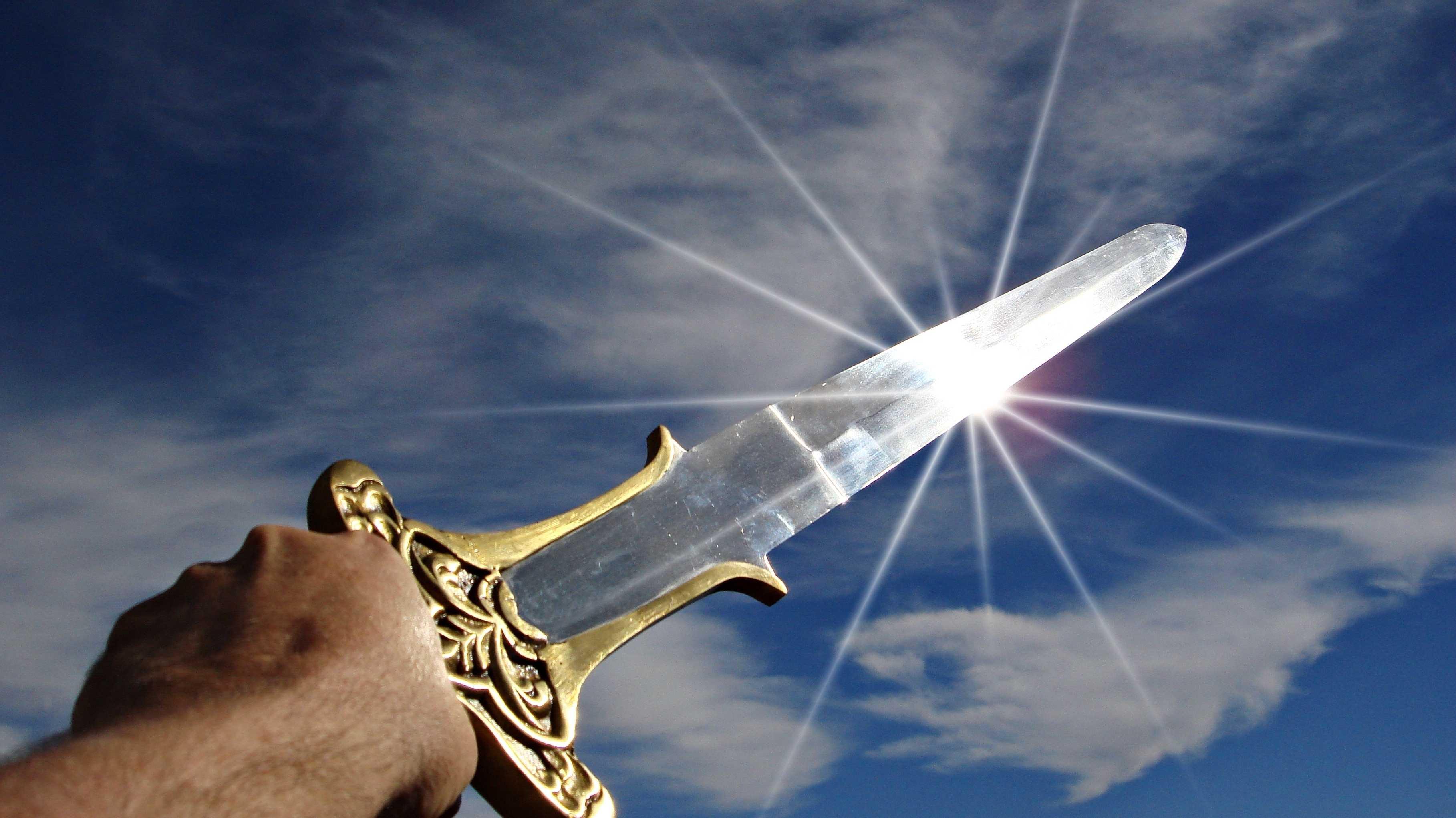 Eine Hand streckt ein blitzendes Schwert gen Himmel